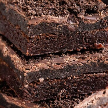 Stack of three Oreo truffle brownies with Oreos around them and recipe title on top of image