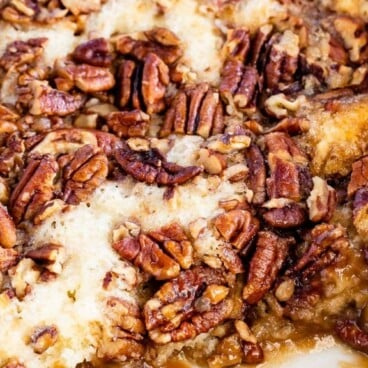 Pecan pie cobbler in a white baking dish with corner piece missing with recipe title on top of image
